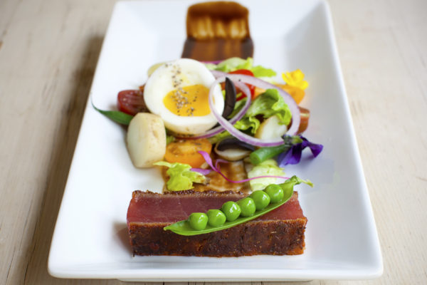 Deconstructed tuna niçoise with spice blackened rare tuna fillet, pea pod & balsamic syrup